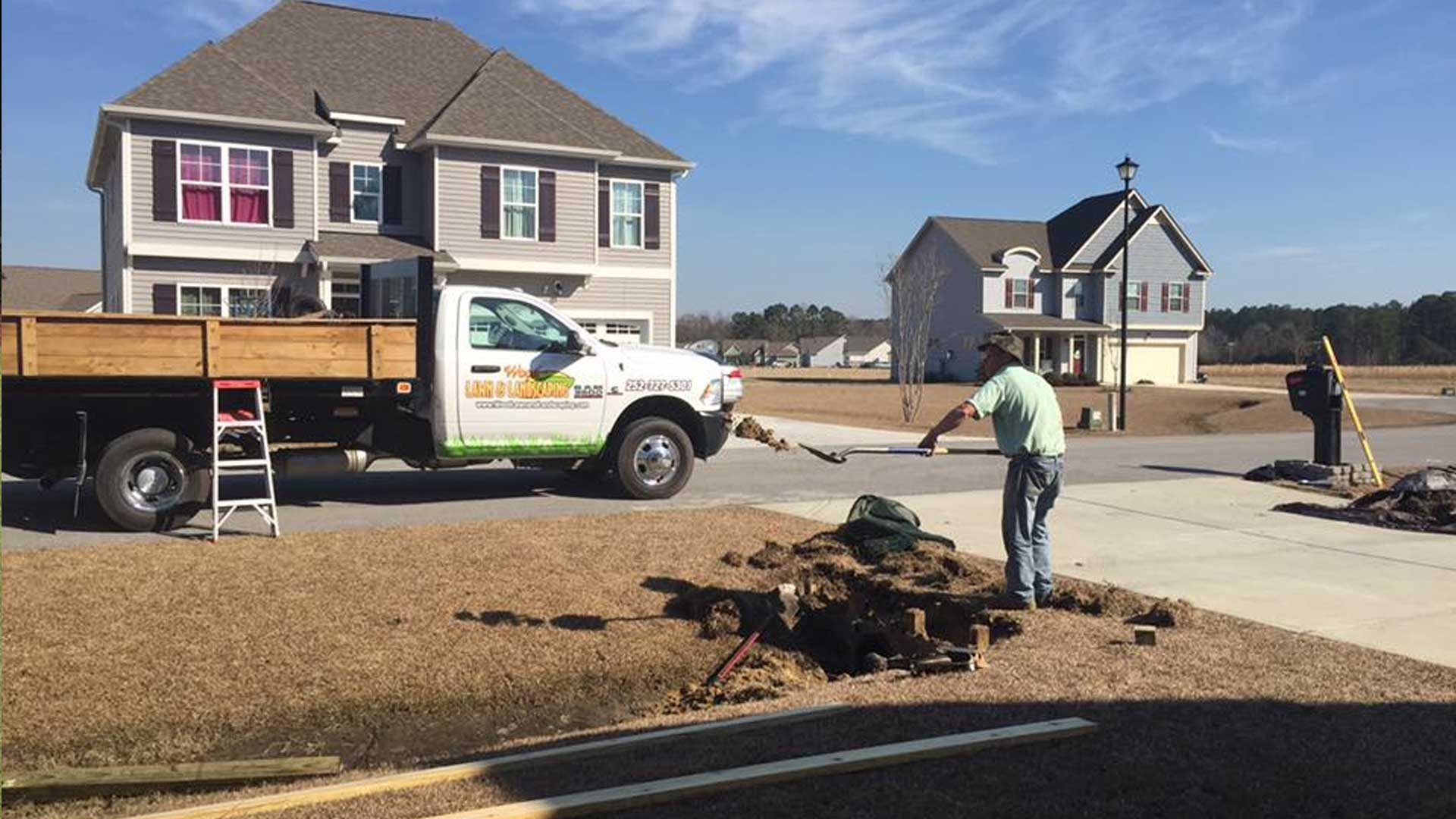 Our employee digging a hole for a new tree installation at a residential property located in Newport, NC.