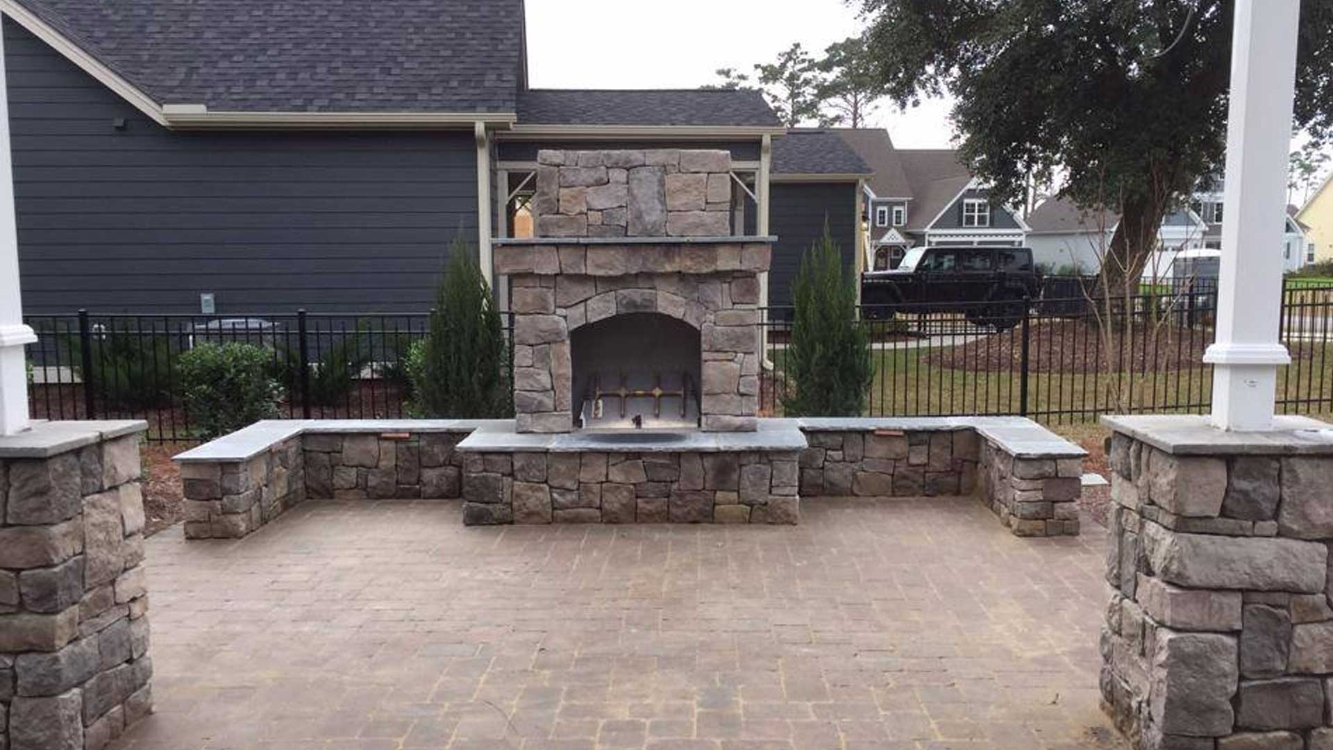 Outdoor fireplace with a paver patio designed and installed by our team of professionals.