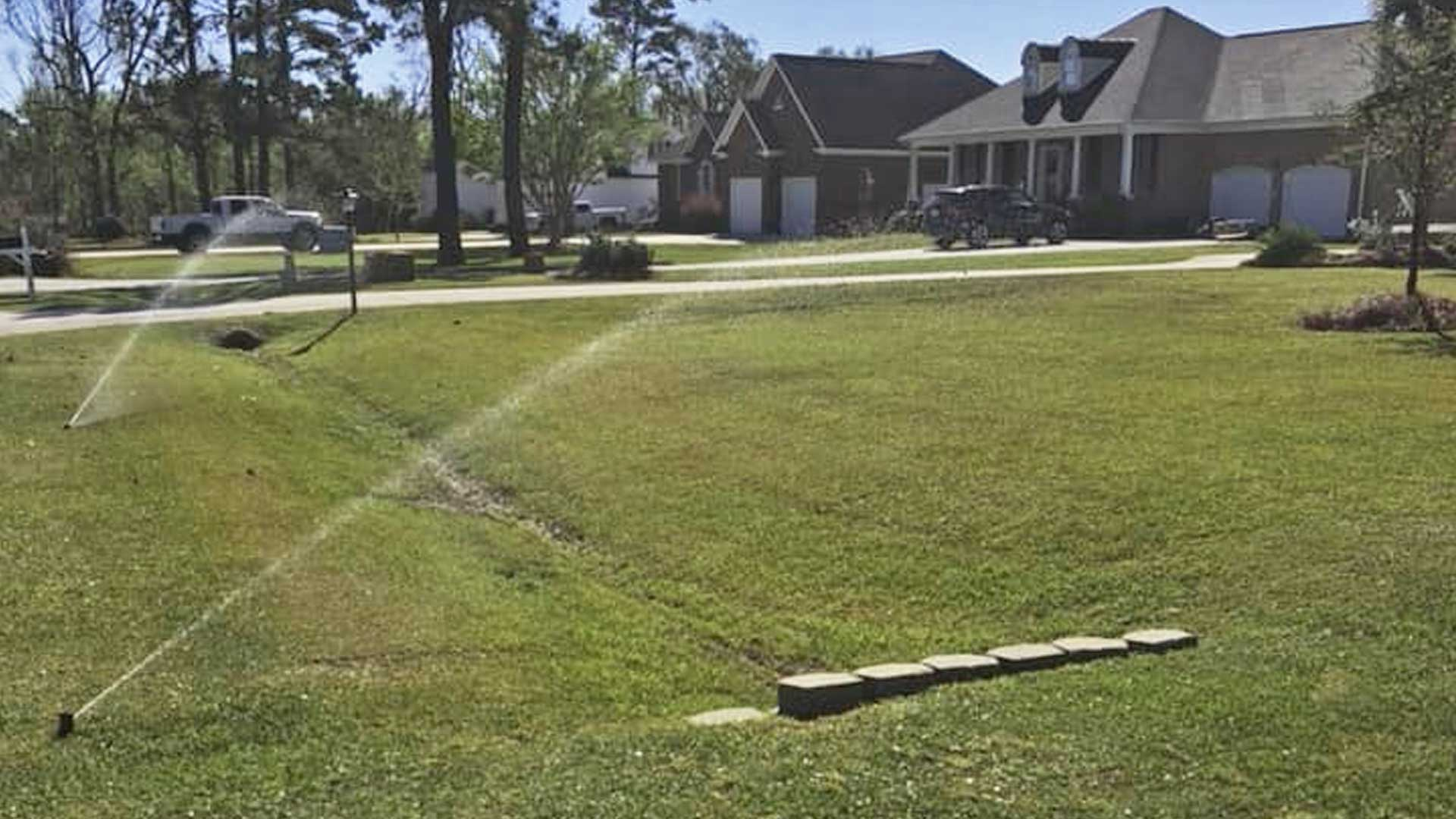Sprinklers watering a residential lawn in Atlantic Beach after we installed a new irrigation system.