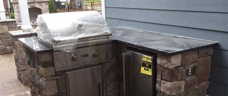 Outdoor kitchen with a built in gas grill, mini fridge, and marble counter top at a residential property in Morehead City.