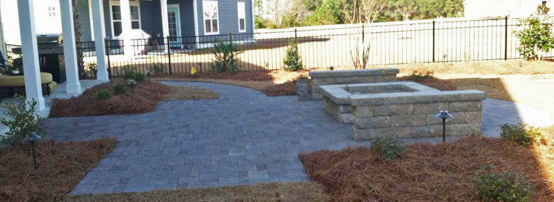 A newly designed and installed fire pit, seating wall, and patio at a home in Atlantic Beach, NC